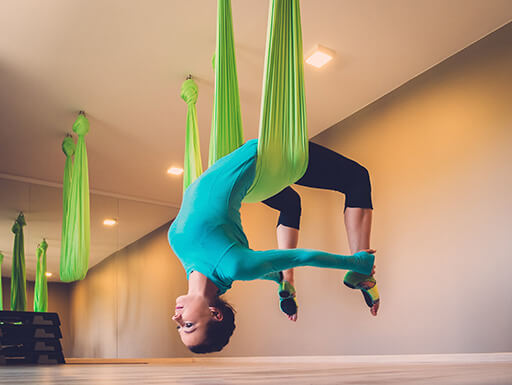 A young woman performs an anti-gravity aerial yoga exercise from green fabric inside of a yoga studio on a spring afternoon.