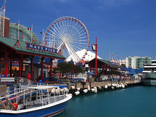 A white ferry and a large, white Ferris wheel are pictured on Navy Pier in Chicago, Illinois on a clear spring day.""
