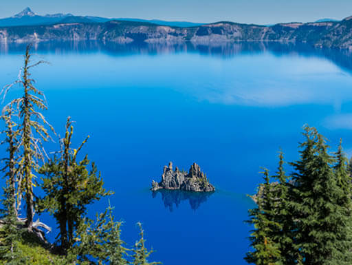 Aerial view of pine trees framing Phantom Ship Island on sunny afternoon in the clear blue waters of Crater Lake National Park in Oregon.