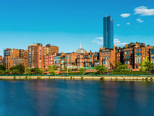 A view across the Charles River of the Boston skyline with Back Bay in the foreground on a bright, sunny day