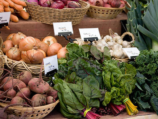 Fresh vegetables in baskets at a farmer's market in California on a bright morning.