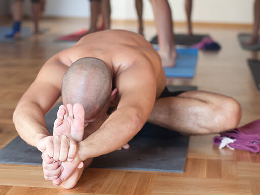 A man stretches on the floor of a yoga studio during an evening class with other yoga students standing behind him.