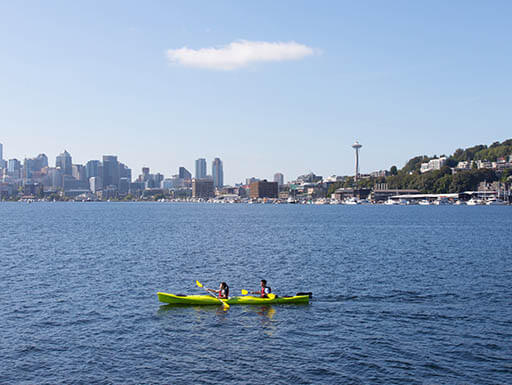 Yellow 2-person kayak on water with Seattle, Washington, skyline in far off distance on clear day