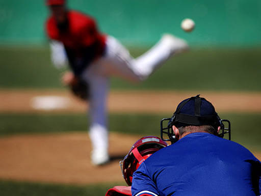 A pitcher in is seen throwing a ball to a catcher, with the umpire standing behind during a baseball game in Washington, D.C.