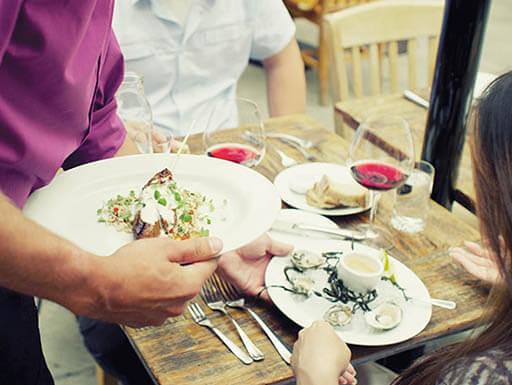 A waiter in a purple shirt serves a couple their food on white plates at a farm-to-table restaurant in San Francisco, California