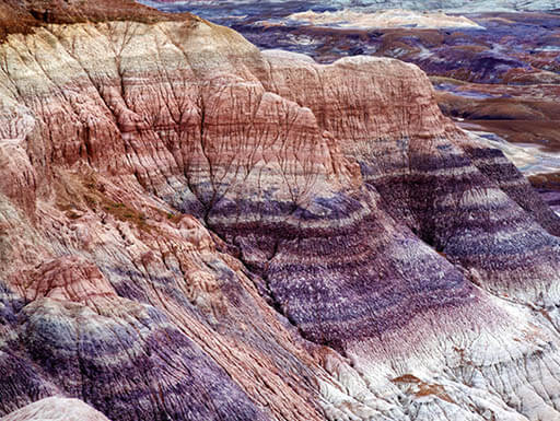 Aerial view of purple striped sandstone of the Blue Mesa badlands in Petrified Forest National Park in Arizona on a cloudy afternoon.