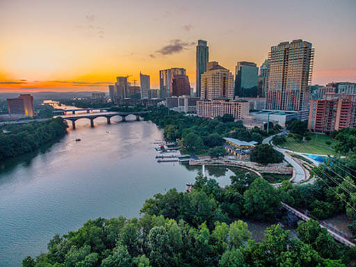 Aerial view of Austin, Texas cityscape along a river at dusk
