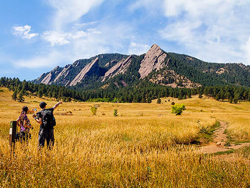Two hikers planning their trek toward the Flatirons in Boulder, Colorado, under blue sky
