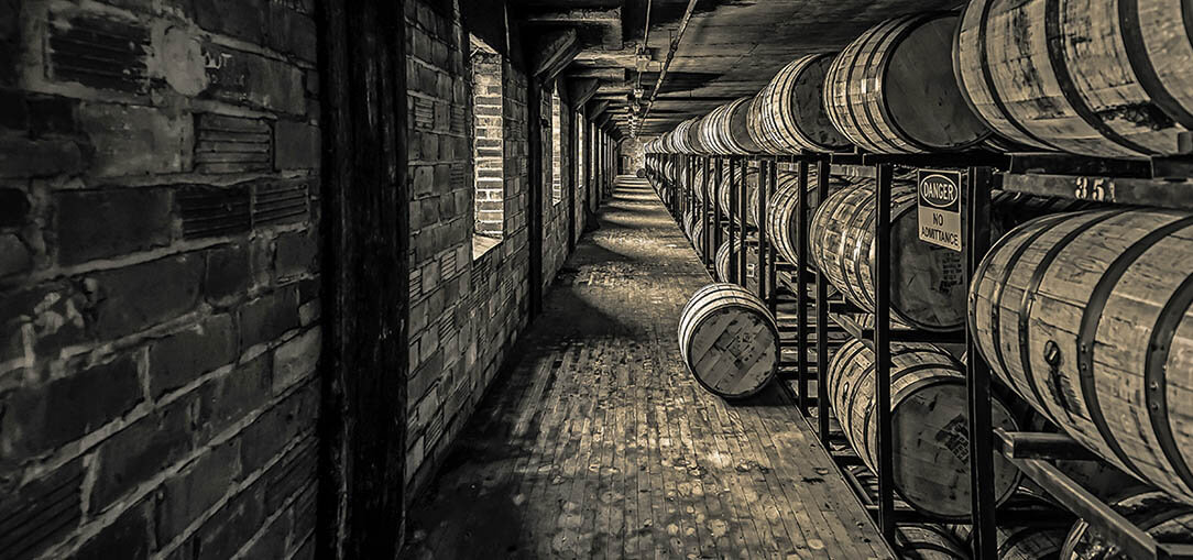 Dark lit room with wooden bourbon barrels stacked on the walls