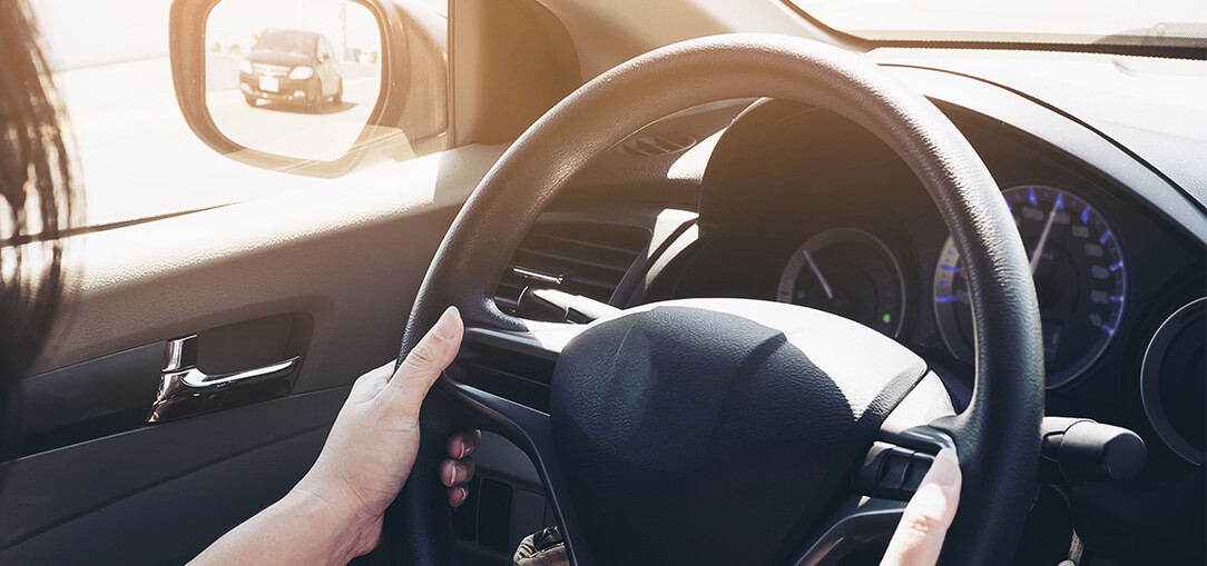 A woman safely drives a car with two hands on the steering wheel on her morning commute