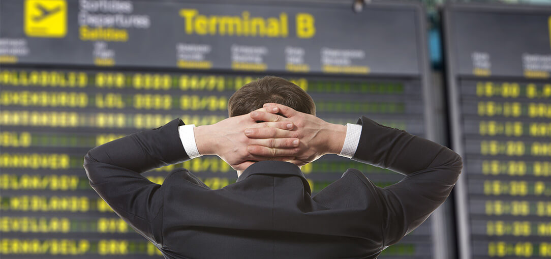 Man wearing a suit with hands behind his head looking at airport departure board on a busy evening in Chicago.