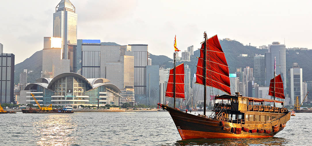 A cityscape view of Hong Kong's plentiful skyscrapers can be enjoyed from colorful red ships in Hong Kong Harbour