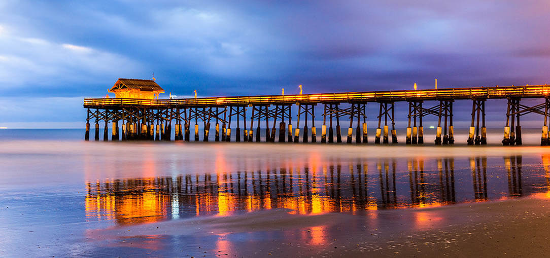 Lights on pier at cocoa beach, florida, at dusk under cloudy skies with the beach reflecting the pier lights and the pink and purple sunset