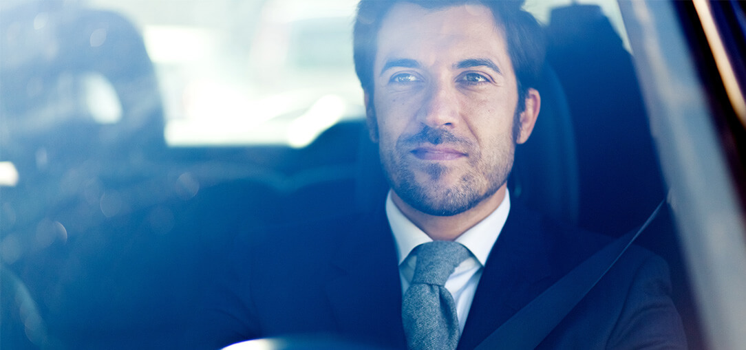 View through front windshield of a car shows a man in a business suit with thoughtful expression on face as he listens to a business podcast, driving a car during daytime.
