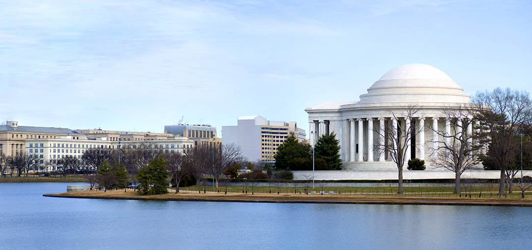 A large body of water is pictured in the foreground, with the Jefferson Memorial and the Washington Monument in the background, against a light blue sky in Washington, D.C