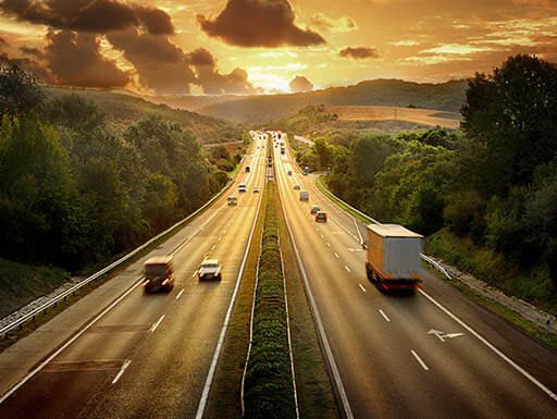 View from above of a highway with four lanes surrounded by lush trees, leading toward the setting sun.