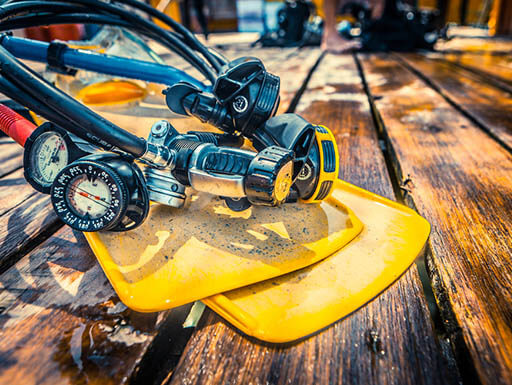 Yellow scuba diving flippers and breathing equipment on a wooden pier