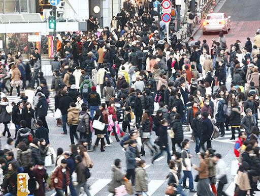 Throngs of people walking in the street in busy Shibuya Crossing