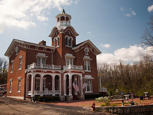 A red brick villa with white, ornate detailing in Galena on a sunny day along the Great River Road Route
