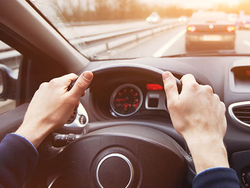 Close up of hands on a steering wheel on a sunny day with a windshield view showing highway traffic.