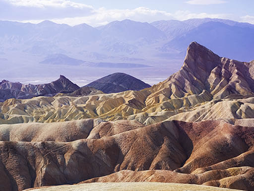 Smooth rocks in various shades of colors sit in Death Valley National Park in California on a sunny afternoon.