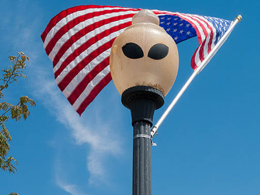 A lamppost stands with alien eyes painted on it, with an American flag waving in the wind behind on a bright afternoon sky in Roswell, New Mexico.