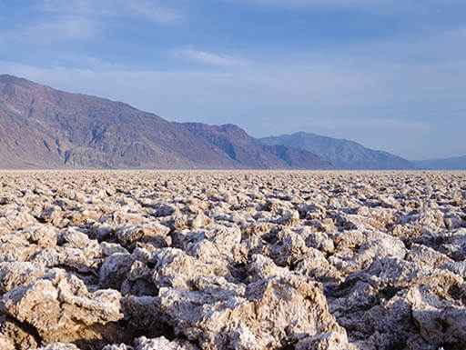 A field of salt rocks on Devil's Golf Course are pictured with a grey mountain in the background at Death Valley in California on an autumn morning.