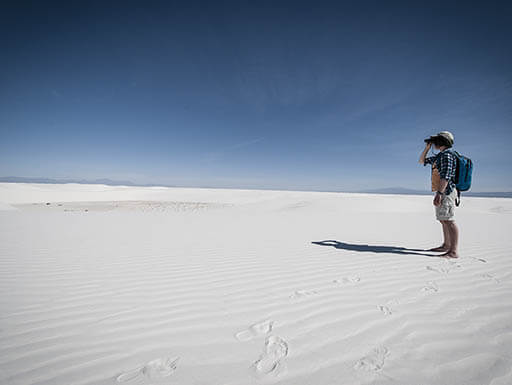 A tourist stands on flat, white sand, looking through binoculars, with a blue morning sky in the background at the White Sands National Monument in New Mexico.