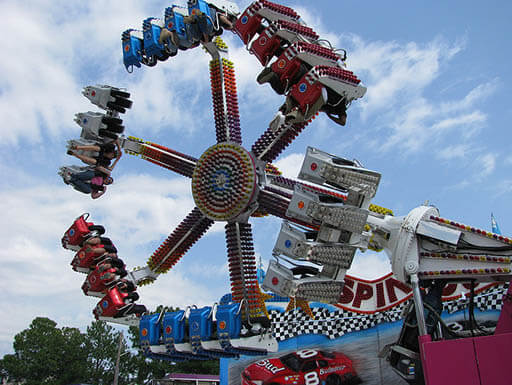 A red, blue and white amusement ride is pictured spinning at the Mississippi State Fair in Mississippi on a bright afternoon.