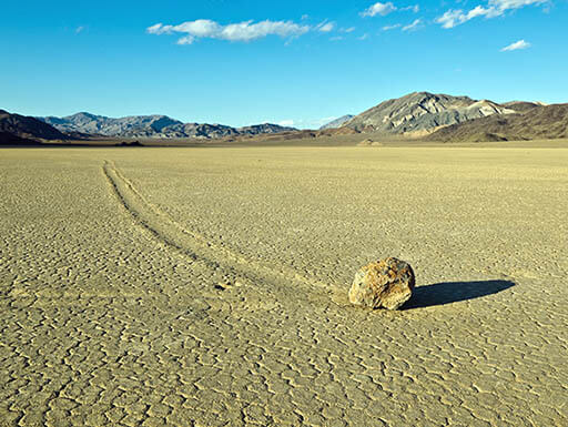 A solo grey sailing stone is pictured in the middle of the desert in Death Valley National Park, California, on a summer afternoon.