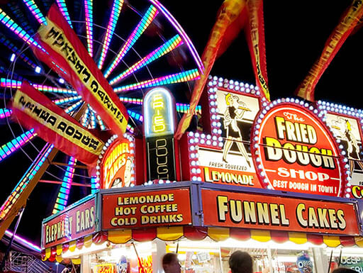 A brightly lit food kiosk is pictured with pink and purple Ferris wheel in the background against a night sky at the North Carolina State Fair in North Carolina