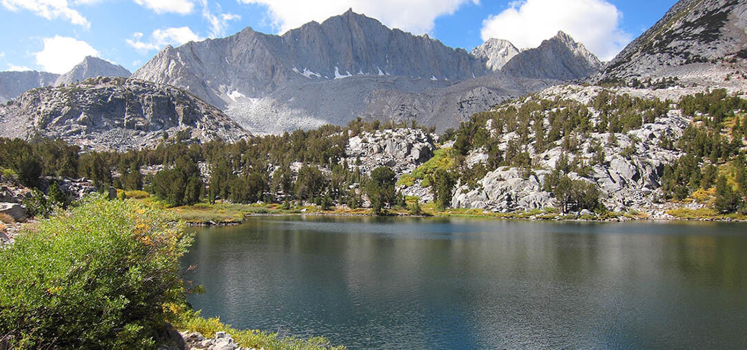 Grey mountains with green trees surround a pristine lake at Sequoia & Kings Canyon National Park in California on a bright afternoon.