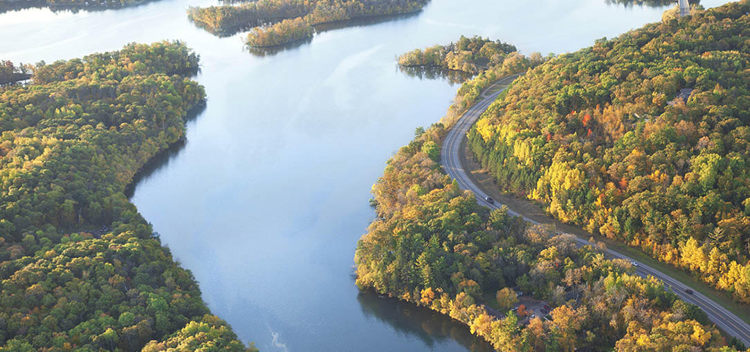 Aerial shot of the Mississippi River beside Great River Road on a sunny day in late summer