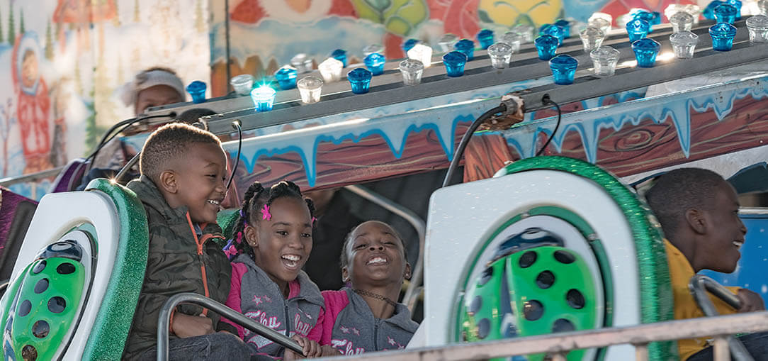 Three children laughing as they enjoy a carnival ride at the Alabama National Fair on a sunny fall afternoon.