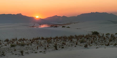 A bright sun is seen in an orange sky as it sets behind the silhouette of mountains at White Sands National Park in New Mexico.