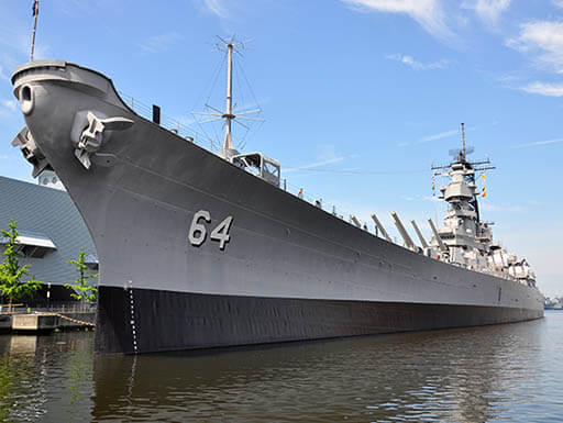 Large, gray USS Wisconsin Battleship (BB-64) floating near the shoreline in Norfolk, Virginia with blue sky in the background