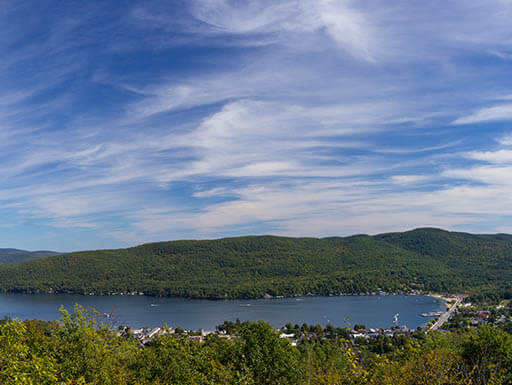 """=""""A view of Lake George, surrounded by green trees and a bright blue sky in the Adirondack region of northern New York."""