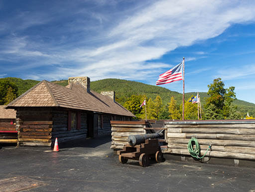 An American flag waves in the wind behind a log fence and matching log building at Fort William Henry Museum and Restoration in Lake George in the Adirondack region of northern New York