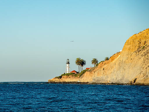 The dark blue waters of the ocean are pictured with a brown cliff on the right side with a lighthouse on its edge and a light, clear blue sky in the background, in Baja California.