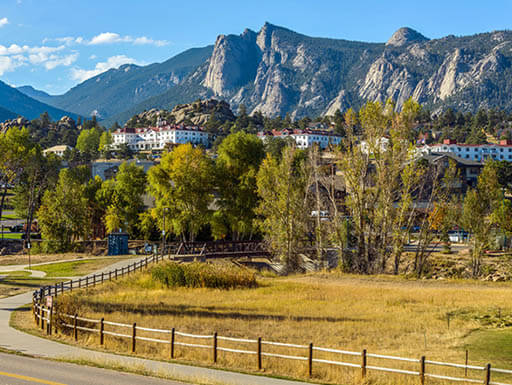 An autumn afternoon in Downtown Estes Park with The Stanley Hotel and Rocky Mountains in the background.