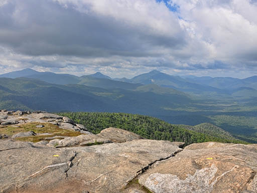 A view from the top of a mountain overlooking green tree-covered mountains and hills at Mount Marcy in the Adirondack region of northern New York