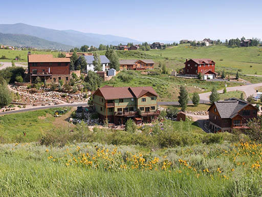 Steamboat Springs in Colorado with small houses on rolling hills under a blue sky.