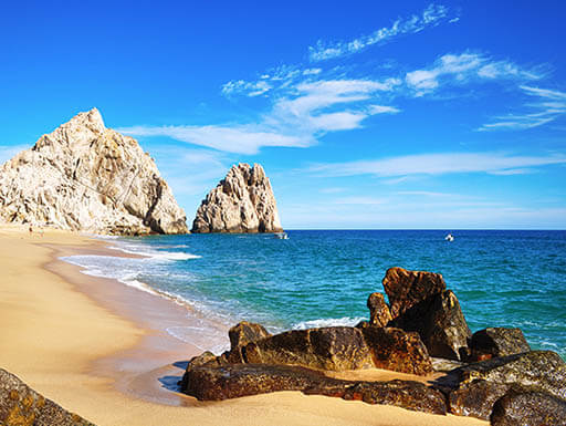 """=""""A light brown sandy beach is pictured with sporadic jagged brown and white rocks, with the aqua blue ocean and tide coming in, at Los Cabos in Baja California."""