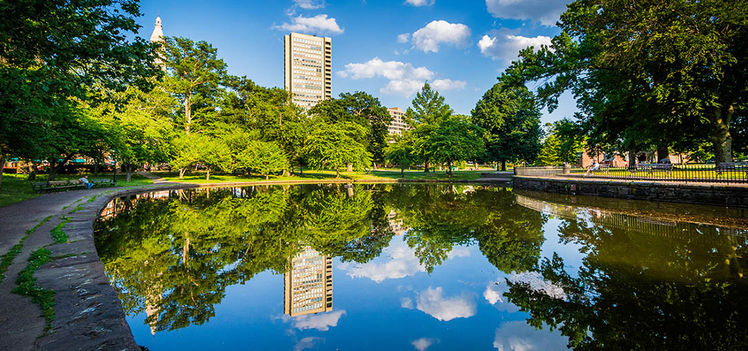 A tall white pillar stands in the center of full, leafy green trees with a bright blue sky, all reflected in the water in the foreground in Bushnell Park Lily Pond in Hartford, Connecticut