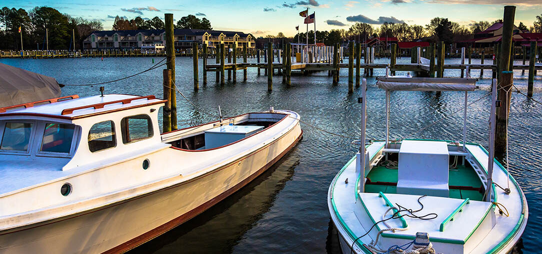 Boats sit in the harbor of St. Michaels, Maryland at sunset
