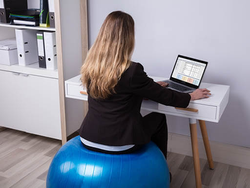 Woman sits on exercise ball while working at desk on laptop.