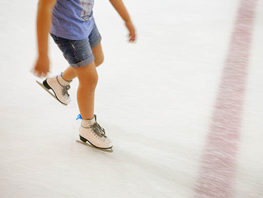 A child is pictured from the shoulders down, wearing a purple T-shirt and jean shorts while skating at an indoor ice rink in Dallas, Texas on a summer afternoon.
