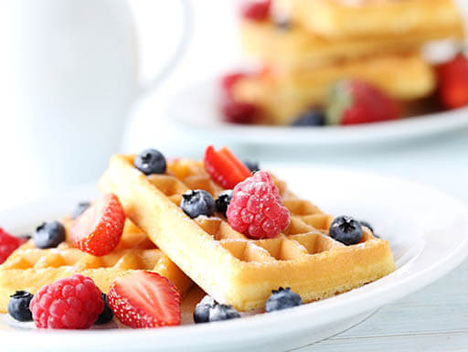 Waffles with blueberries and raspberries on white plate