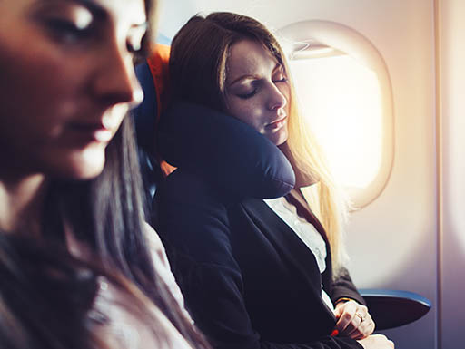 Two business women traveling on airplane. One woman sleeps, reclining her head on neck pillow