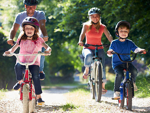 Young couple and two kids ride bikes on sunny day.